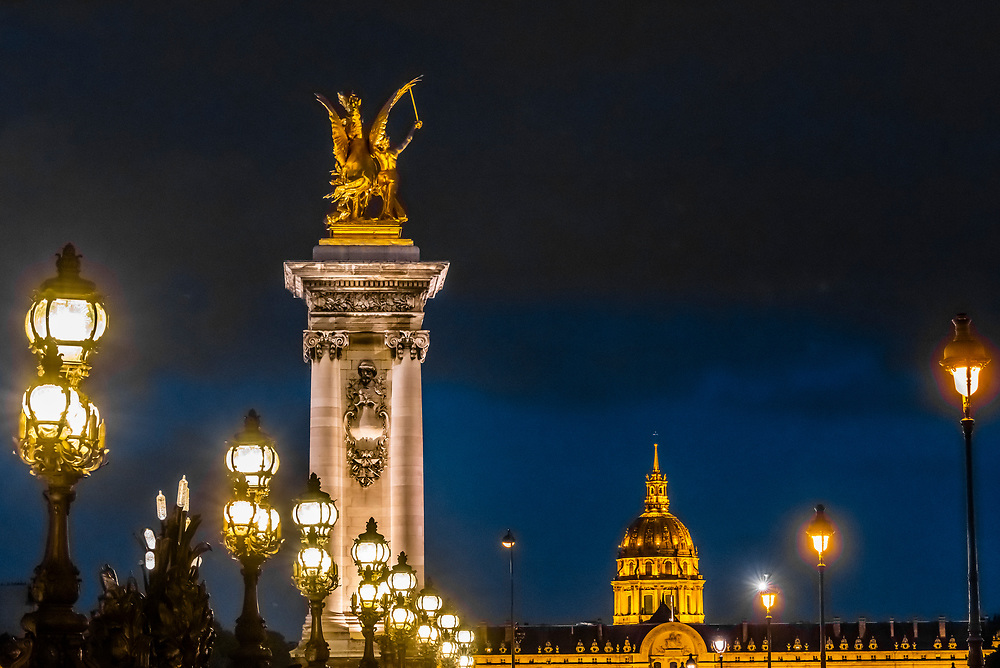 Pont Alexandre III (bridge) with its Art Nouveau lamps and behind, gilded sculptures with winged horses and in background Hotel des Invalides, Paris, France.