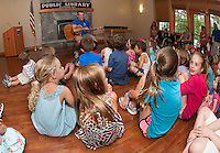 """Paul Warnick entices youngsters to """"Dream Big"""" for the start of Gilford Library's Summer Reading Program Monday afternoon.   (Karen Bobotas/for the Laconia Daily Sun)"""
