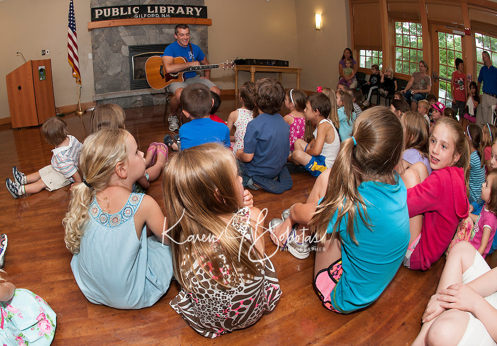 "Paul Warnick entices youngsters to ""Dream Big"" for the start of Gilford Library's Summer Reading Program Monday afternoon.   (Karen Bobotas/for the Laconia Daily Sun)"