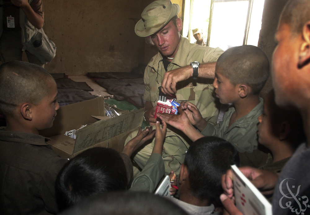 A U.S. Army civil affairs soldier hands out donated toys and school supplies during a U.S. military civil affairs mission July 10, 2002 at the Charikar Childrens Orphanage in Charikar, Afghanistan. The civil affairs personnel handed out school supplies, toys, and candy to nearly 100 young Afghan boys and girls who live at the orphanage, which is located near the Bagram Airbase.