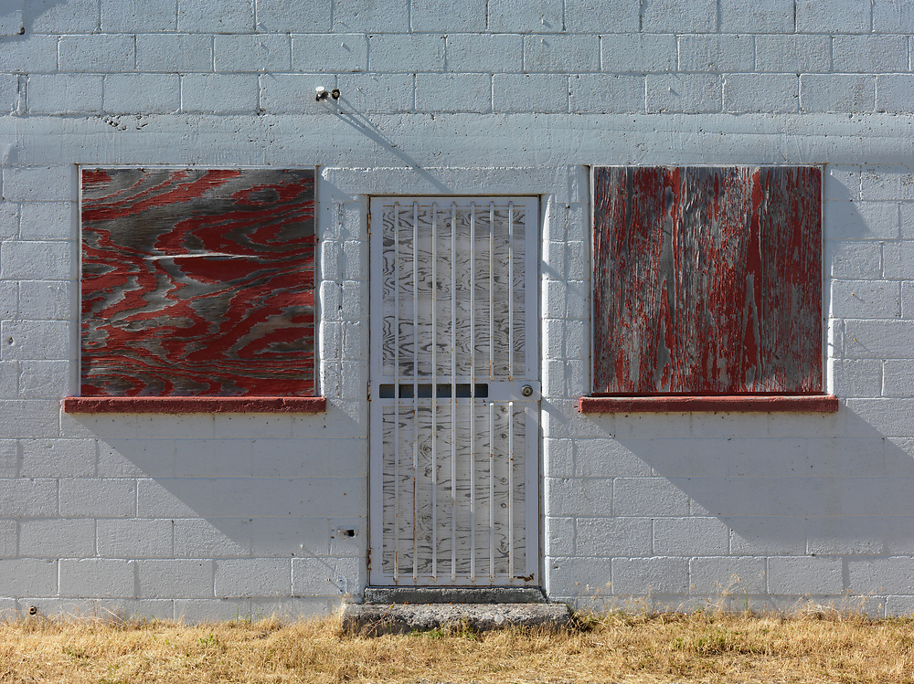 Boarded windows and locked door on white cinder block building roadside in Eastern Idaho