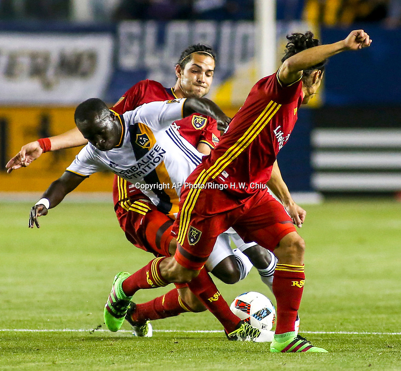 Los Angeles Galaxy forward Emmanuel Boateng, center, struggle for the ball defended by Real Salt Lake midfielder John Stertzer, back, and defender Tony Beltran, front,  in the first half of an MLS soccer game in Carson, Calif., Saturday, April 23, 2016. (AP Photo/Ringo H.W. Chiu)
