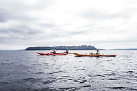 Two women and a man paddling sea kayaks from Blake Island across the Puget Sound to West Seattle with the north end of Vashon Island in the background, Washington State, USA.