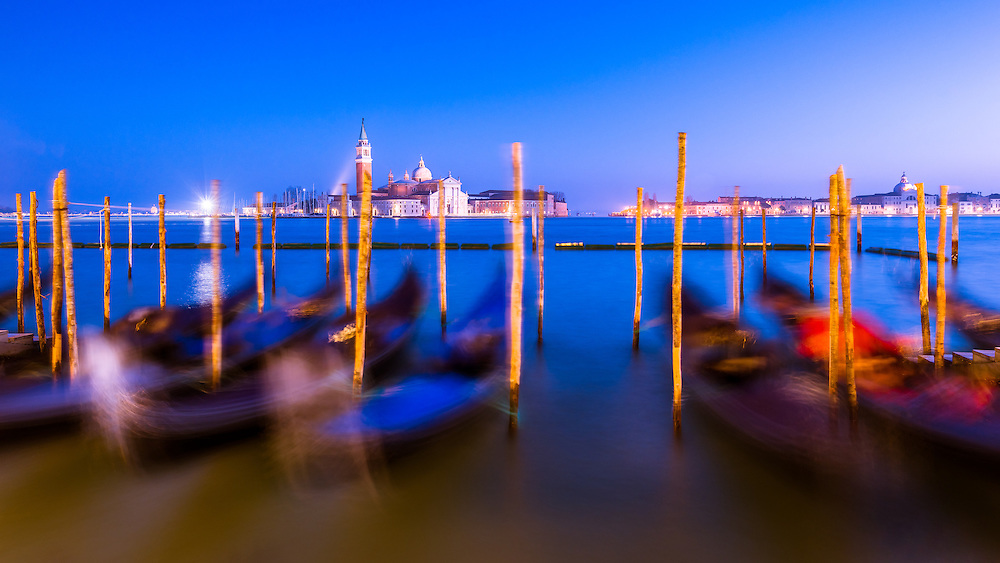 gondolas line the bank at st mark's square in venice during blue hour. The image is a long exposure causing the gondolas to become blurred and illustrating their movement on the water