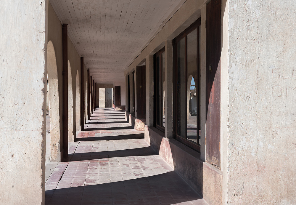 Sunlight shines through the archways of an outdoor passage around old buildings.