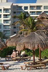 10 Feb 2014. Cancun, Mexico.<br /> A tourist sits under thatch umbrellas on the tourist beach at Isla Cancun along the Zona Hotelera on the Carribean Sea. <br /> Photo; Charlie Varley/varleypix.com