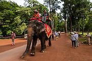 Tourists ride an elemphant around Bayon temple.