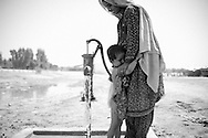 A mother bathes her child by a water pump at a camp site housing flood victims. Lack of hygiene is one of the biggest problems in the camps at the moment. Sukkur, Pakistan, 2010