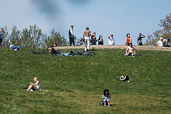 © Licensed to London News Pictures. 23/04/2020. London, UK. People relaxing and sunbathing on Primrose Hill, north London during a pandemic outbreak of the Coronavirus COVID-19 disease. The public have been told they can only leave their homes when absolutely essential, in an attempt to fight the spread of coronavirus COVID-19 disease. Photo credit: Ben Cawthra/LNP. Photo credit: Ben Cawthra/LNP