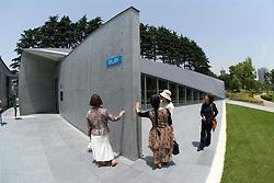 Visitors examine wall at 21_21 Design Sight art gallery at Tokyo Midtown park in Tokyo