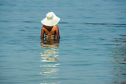 Female Holiday maker enters the water at the Dead Sea, Israel