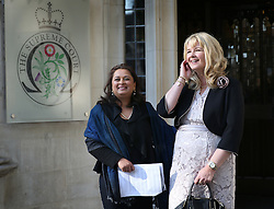 © Licensed to London News Pictures. 14/10/2015. London, UK.  Alison Sharland (R) and Varsha Gohil stand outside the Supreme Court. A ruling has stated that they are entitled to more money in their divorce settlements after their husbands hid the true state of their wealth.  Photo credit: Peter Macdiarmid/LNP
