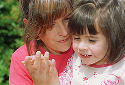 Young girl with autism touching mother's hand,