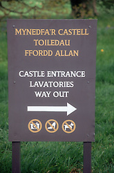 Bilingual sign which gives directions to Castle Entrance; Lavatories and Way Out,