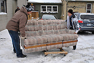 Two men move a sofa on a dolly while another man looks on at the Worth a Second Look parking lot in Kitchener, Ontario, Canada. The men are part of Job Cafe, a program of The working Centre.
