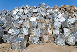 Pile of tins baled up at a metal recycling centre waiting to be sold on and remelted,