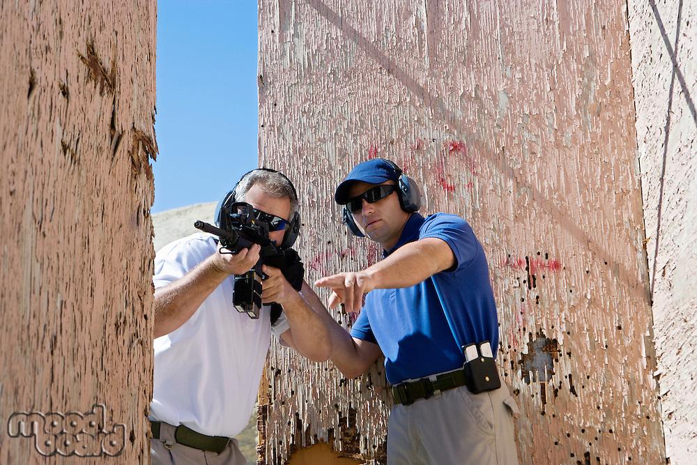 Instructor assisting man aiming machine gun at firing range