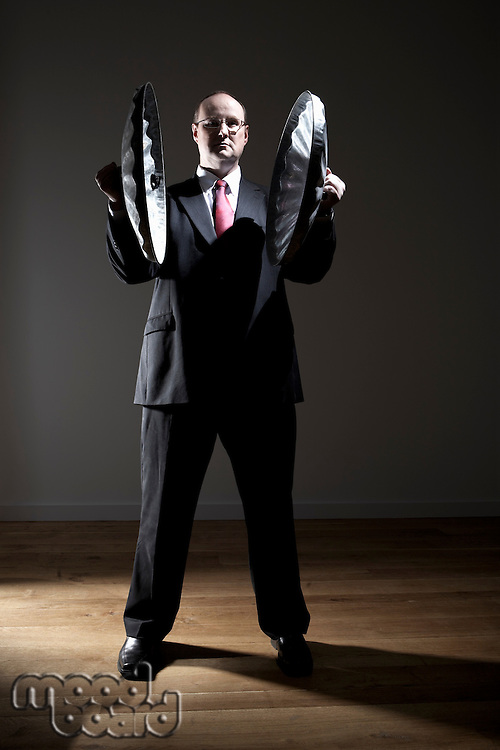 Man in full suit holding two garbage can lids