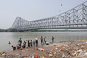 People washing in the ocean, Howrah Bridge in background. Calcutta. India.