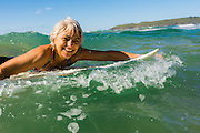 Woman surfer paddling her surfboard in the surf, Sandy Beach, Coffs Harbor, NSW, Australia ***Model Release available