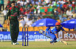 September 20, 2018 - Abu Dhabi, United Arab Emirates - Afghanistan cricketer Hashmatullah Shahidi dives in to complete a run as Bangladesh cricket captain Mashrafe Mortaza looks on during the 6th cricket match of Asia Cup 2018 between Bangladesh and Afghanistan at the Sheikh Zayed Stadium,Abu Dhabi, United Arab Emirates on September 20, 2018. (Credit Image: © Tharaka Basnayaka/NurPhoto/ZUMA Press)