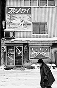 An elderly local resident walks past a building decorated with a poster for the film Blue Hawaii in Yubari City, on the northernmost island of Hokkaido in Japan. The city, once well known for its international film festival, is today bankrupt.