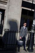 A stylish young man stands with a briefcase looking confident on a Mayfair street corner in central London.