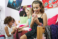 Fashionable Young Girls Applying Makeup in trendy bedroom