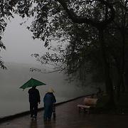 An elderly couple walk beside Hoan Kiem Lake, Hanoi, Vietnam. Hanoi is the capital of Vietnam and the country's second largest city. Hanoi, Vietnam. 17th March 2012. Photo Tim Clayton