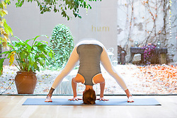 Woman Practicing Yoga, Wide-legged forward bend pose
