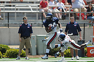 Blue team running back Brandon Bolden (34) is tackled by Red team defender Dele Junaid in Mississippi's Grove Bowl in Oxford, Miss. on Saturday, April 17, 2010.