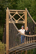 "- Mulvane, Kansas, USA - Larry Richardson was so impressed with San Francisco's Golden Gate Bridge that he built a replica of it in his backyard at his home in Mulvane, Kansas.<br />            ""People have said: Are you crazy? But, hey, how many people can say they've got a replica of the Golden Gate Bridge in their backyard. I don't know of anyone else in America who's got one,"" the 63 year old retired mailman <br />            Unlike the real bridge, which is 8,981 feet long and 692 feet high, Larry's bridge is 150 feet long, 25 feet high and 8 feet wide, and his is made of wood – not steel.<br />            But, it's still so impressive that he gets lots of visitors who flock to his home to marvel at it. ""They get a kick out of it. They really enjoy it,"" he said.<br />            Larry's had a life long fascination with the Golden Gate Bridge. ""I really love that bridge. There's just something about it. Some people admire mountains. I've always been fascinated with that bridge. It really is a magnificent structure,"" he said.<br />            So when Larry decided he wanted to build a bridge over a creek on the 5 acres of land he owns, he thought: Why not build a replica of the Golden Gate bridge he so loves.<br />            ""I could have built a simple foot bridge. But, anyone can build a foot bridge. I thought: Why not build one bigger, something special like the Golden Gate Bridge? I thought it'd be a challenge,"" he explained.<br />            Larry has no engineering training. But, he grew up on a farm. ""If you grow up on a farm, you learn how to fix things. So I figured I could do it,"" he said.<br />            Instead of architectural drawings, Larry used a postcard of the Golden Gate Bridge to see what he needed to do. ""Yes, that's all I had to go on - a postcard,"" he said.<br />            He started building his bridge in 1994 and with the help of his late father Norman and brother Lee. They had it finished by 2001. The 3 of them often worked 20 to 30 hours a week"