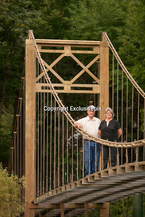 """- Mulvane, Kansas, USA - Larry Richardson was so impressed with San Francisco's Golden Gate Bridge that he built a replica of it in his backyard at his home in Mulvane, Kansas.<br />            """"People have said: Are you crazy? But, hey, how many people can say they've got a replica of the Golden Gate Bridge in their backyard. I don't know of anyone else in America who's got one,"""" the 63 year old retired mailman <br />            Unlike the real bridge, which is 8,981 feet long and 692 feet high, Larry's bridge is 150 feet long, 25 feet high and 8 feet wide, and his is made of wood – not steel.<br />            But, it's still so impressive that he gets lots of visitors who flock to his home to marvel at it. """"They get a kick out of it. They really enjoy it,"""" he said.<br />            Larry's had a life long fascination with the Golden Gate Bridge. """"I really love that bridge. There's just something about it. Some people admire mountains. I've always been fascinated with that bridge. It really is a magnificent structure,"""" he said.<br />            So when Larry decided he wanted to build a bridge over a creek on the 5 acres of land he owns, he thought: Why not build a replica of the Golden Gate bridge he so loves.<br />            """"I could have built a simple foot bridge. But, anyone can build a foot bridge. I thought: Why not build one bigger, something special like the Golden Gate Bridge? I thought it'd be a challenge,"""" he explained.<br />            Larry has no engineering training. But, he grew up on a farm. """"If you grow up on a farm, you learn how to fix things. So I figured I could do it,"""" he said.<br />            Instead of architectural drawings, Larry used a postcard of the Golden Gate Bridge to see what he needed to do. """"Yes, that's all I had to go on - a postcard,"""" he said.<br />            He started building his bridge in 1994 and with the help of his late father Norman and brother Lee. They had it finished by 2001. The 3 of them often worked 20 to 30 h"""