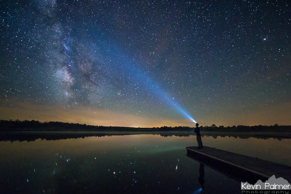 The stars of the milky way galaxy are reflected in a calm pond outside of Keosauqua, Iowa. Southeast Iowa has some of the darkest skies in the Midwest, perfect for stargazing. In this self portrait, I stood on the end of a dock and pointed my headlamp towards the stars. Because it was a humid night with fog moving across the water, the beam of light showed up well.<br /> <br /> Date Taken: June 25, 2014