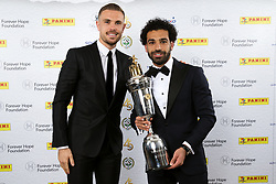 Liverpool's Mohamed Salah and Jordan Henderson (left) pose with the PFA Player Of The Year Award Trophy during the 2018 PFA Awards at the Grosvenor House Hotel, London