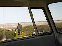 Couple walking towards camper van from beach view through camper van window