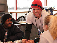 "(left to right) Dominque Wright, Joe Melendrez and Trish Graham share a monemt at a burrito party for the homeless hosted by U.D. Religious Studies student Joe Melendrez at Chipotle's on Brown Street in Dayton.  Trish says she met Joe at a fall breakout in New Orleans, and they have been ""best friends ever since."""