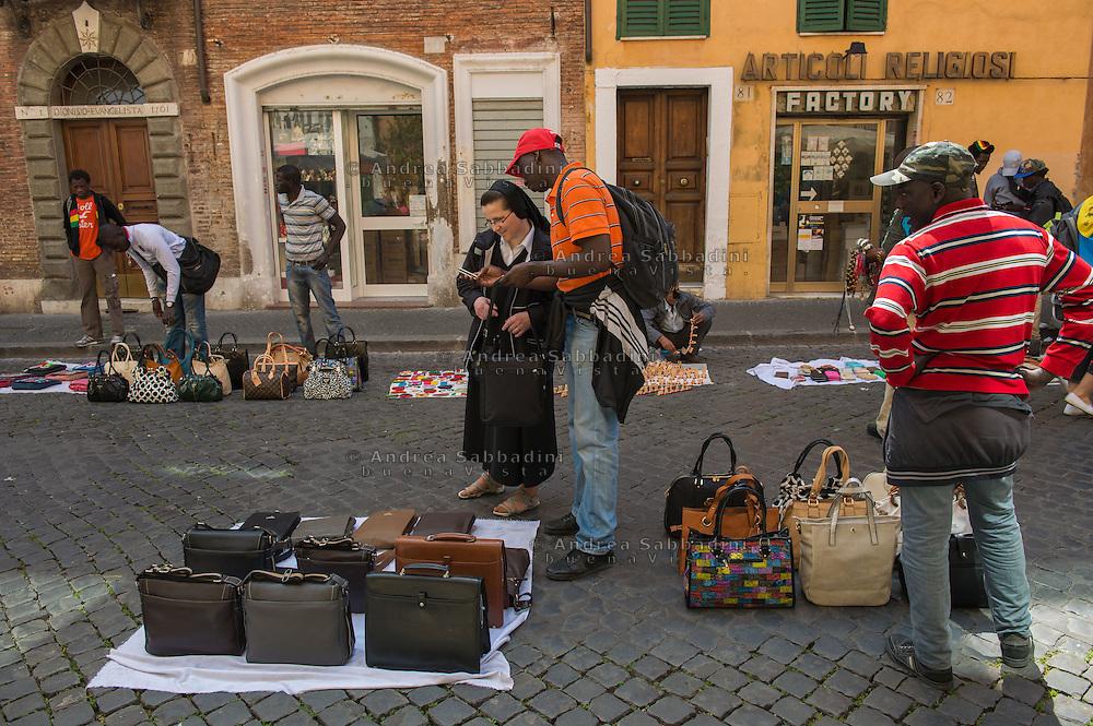 Roma, 26/04/2014: immigrati nord africani vendono borse e accessori contraffatti, Borgo Pio - immigrants from north Africa sell fake pruduct, Borgo Pio
