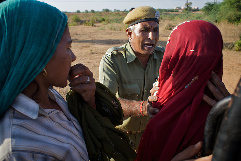 A forest guard attempts to arrest two women caught collecting fire-wood from Rantambore National Park. The depletion of habitat by human activities like fire-wood collection is of particular concern to advocates of tiger conservation. ..Sariska National Park in Rajasthan was once home to dozens of tigers but by 2005 poaching had resulted in their complete eradication. Recognising the urgent need for intervention, the Indian and Rajasthan-state governments began the reintroduction of tigers into Sariska. Two cats were airlifted 200 km from Ranthambore National Park in June 2008. On November 5th an attempt to relocate a third tiger was postponed until later in the month. This relocation strategy is certainly an important part of the tiger conservation effort but many, including those like Dharmendra Khandal of the NGO Tiger Watch, argue that it will never be entirely successful without properly confronting the three essential issues that threaten tiger populations: poaching, habitat loss and the hunting of prey-base animals. In turn, these three issues cannot be addressed without acknowledging the malign influence of caste, poverty and poor administrative accountability. Poaching is almost exclusively undertaken by extremely poor and marginalised groups, including the Mogia caste who, without education, land and access to credit have limited alternative means of income. Many in the Mogia community also hunt bush meat for both their own consumption and to sell to others. This results in a depletion of the prey-base upon which tigers feed. Encroachment and grazing by those including the Gujar people who raise dairy herds, have led to habitat loss in Sariska and other parks. To properly tackle the problem of hunting and encroachment, the government must provide alternative livelihoods for marginalised groups and relocate them to viable land before - rather than after - the re-introduction of tigers. Compounding all these issues is the ridged hierarchy of India's forest d