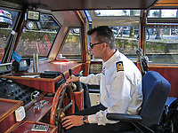 Captain at the wheel of a canal cruise boat, Amsterdam, Holland, Netherlands, 200710050111.<br />