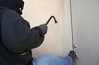 Burglar kicking door of house