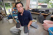 Craftsman Yorio Takahashi poses for a photo with ink stones made from local slate that was rescued from the debris at his temporary workshop in Ogatsu, Ishinomaki City, Japan on 9 Sept. 2012.  Photographer: Robert Gilhooly