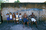 Group of kids leaning against a wall covered in graffiti, two kids sitting on bikes, Brazil, 2000's