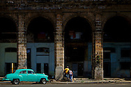An old green car parked outside the big arcades that are só typical of Centro Habana.
