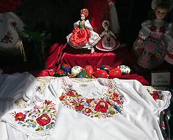 Hungarian embroidery on handmade blouse plus a souvenir doll in traditional Hungarian costume light up the window of a souvenir store on Vaci Street, Budapest, Hungary.  This pedestrians-only shopping street is the prime tourism area of the city.