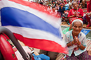 "May 12 - BANGKOK, THAILAND: Women pray in front of the Thai flag at the Red Shirts' main stage Wednesday afternoon. The Thai government said Wednesday that time has run out for ""Red Shirt"" protesters in Ratchaprasong and Sala Daeng intersections in Bangkok and that a crackdown could come at any time. As news of the anticipated crackdown spread, Red Shirt protesters continued with an almost festive mood at their main stage but many of the sleeping areas around the protest site appeared to be empty. No official estimates on crowd size are available.  Photo by Jack Kurtz"