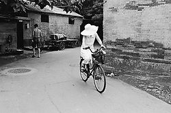 Lady riding bicycle in summer in a traditional Beijing hutong