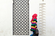 TETOUAN, MOROCCO - 6th April 2016 - Lady wearing colourful clothing walks past a bright whitewashed wall and metal geometric arch pattern in the Tetouan Medina, Rif region of Northern Morocco.