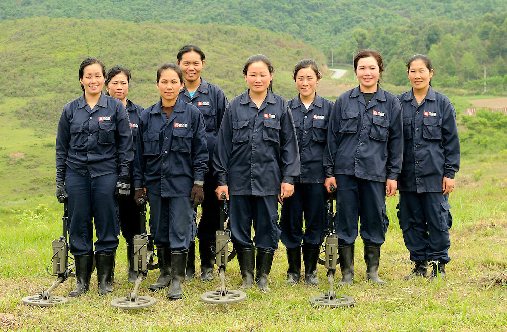 "Mines Advisory Group (MAG) women's team in Nong Het, Laos...Laos was part of a ""Secret War"", waged within its borders primarily by the USA and North Vietnam.  Many left over weapons supplied by China and Russia continue to kill.  However, between 90 and 270 million fist size cluster bombs were dropped on Laos by the USA, with a failure rate up to 30%.  Millions of live cluster bombs still contaminate large areas of Laos causing death and injury.  The US Military dropped approximately 2 million tons of bombs on Laos making it, per capita, the most heavily bombed country in the world. ..The women of Mines Advisory Group (MAG) work everyday under dangerous conditions removing unexploded ordinance (UXO) from fields and villages...***All photographs of MAG's work must include (either on the photo or right next to it) the credit as follows:  Mine clearance by MAG (Reg. charity)***."