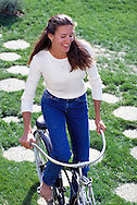 Young woman bicycling through a park.